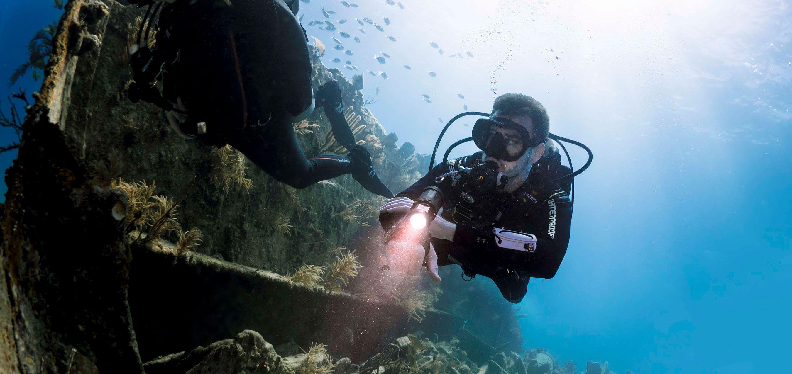 SDI-Divers-Exploring-Wreck-with-Flashlight-Photo.jpg